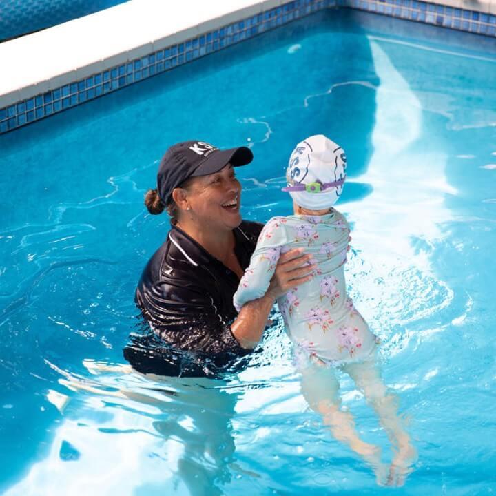 Kattya teaching toddler to swim