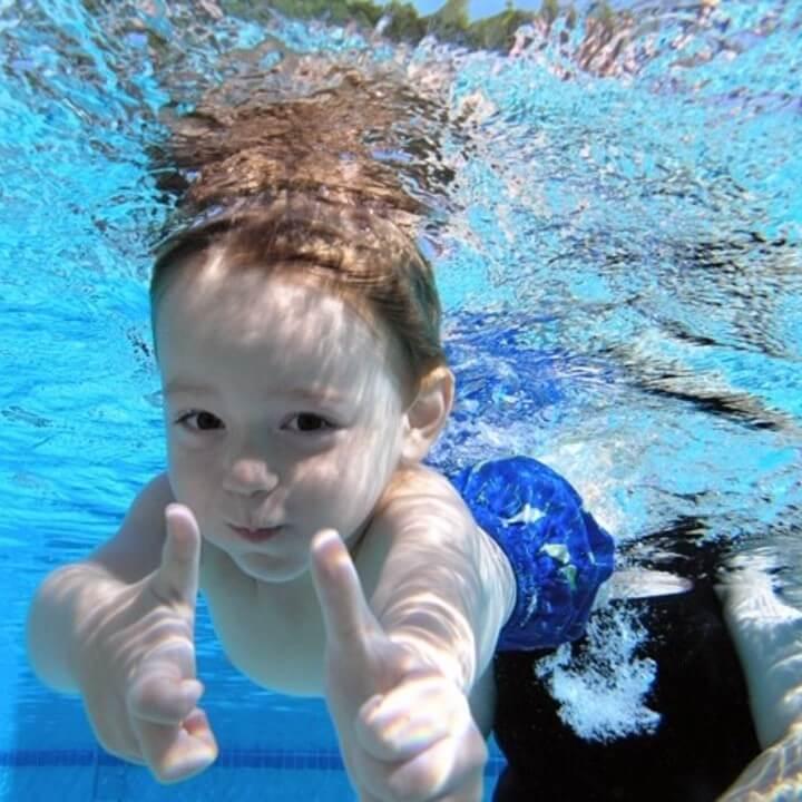 Confident boy pointing underwater