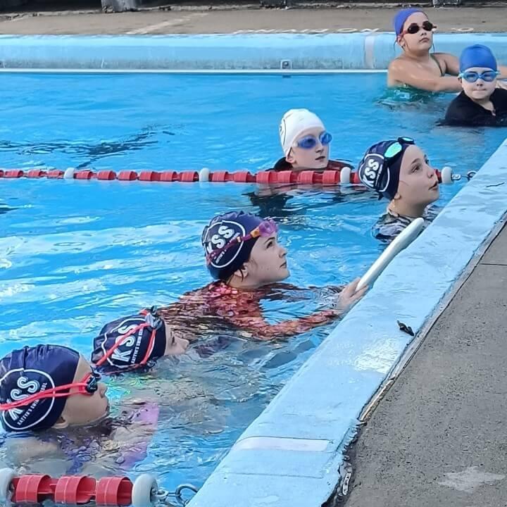 Swim clinic kids listening to instructions