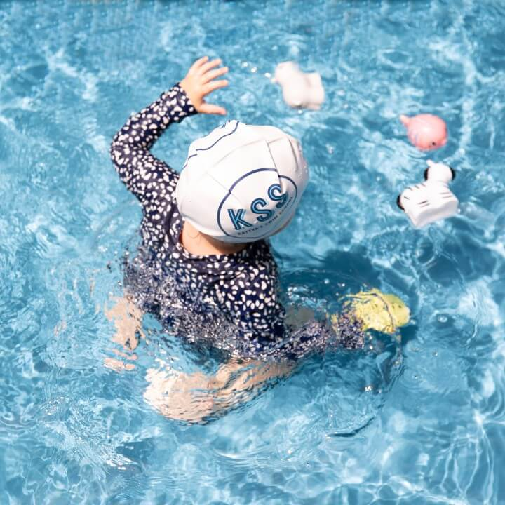 Toddler enjoying playing with toys in the water