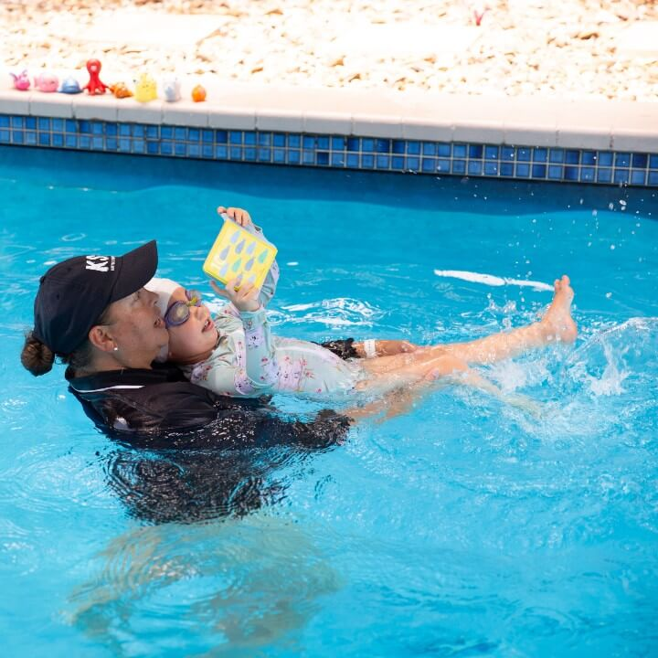 Child kicks in the water whilst reading book